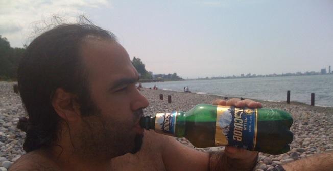 Sahilde bir litrelik Gürcü birası Mitieli içen Türk genci-Arkada Batum silüeti