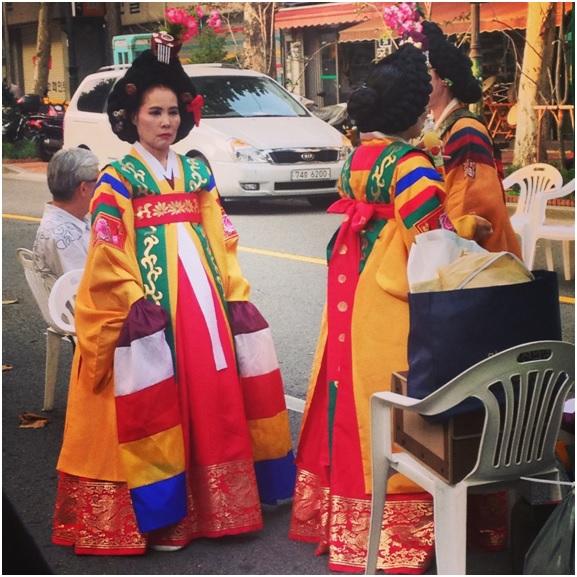 Seul'de bir sokak festivali, ve sıralarını bekleyen yerel kıyafetli kadınlar