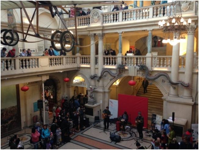 Bristol Müzesi – Çin yeni yılı Kutlamaları Sırasında / Müzisyenlerin solunda duran kafasına kova geçirilmiş heykel Banksy.